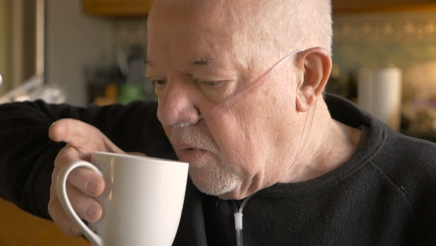 A senior man drinking coffee while wearing oxygen supplementation in slowmo