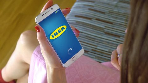 young woman holding a cell phone with loading ikea mobile app conceptual editorial 4k clip