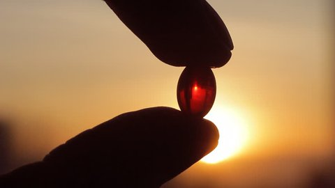 Men fingers holding magic red pill vitamin E capsule against sunset. Reality, medicine and pharmacy concept