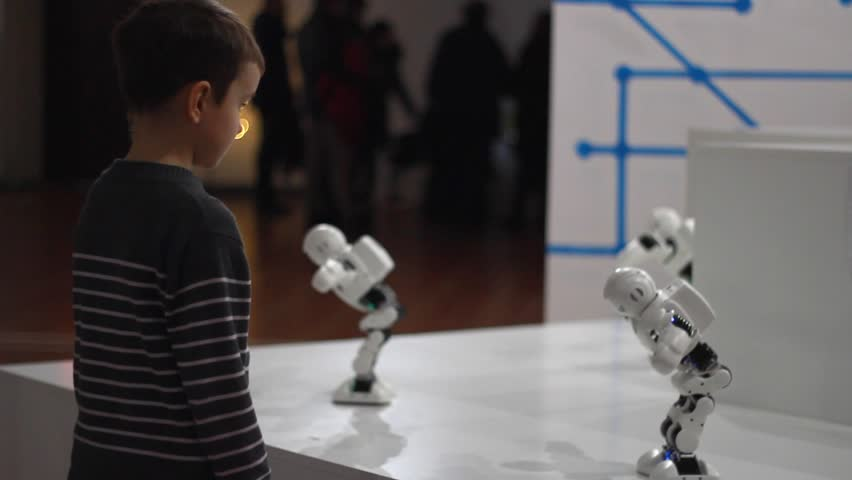 Robot and child. Boy looking for dancing robot. Kid boy watching robot dance. Boy look at robotic technology at exhibition. Boy and group of robot toy