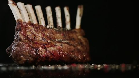 SLOW MOTION FOOD: spices fall on the rack of lamb close up