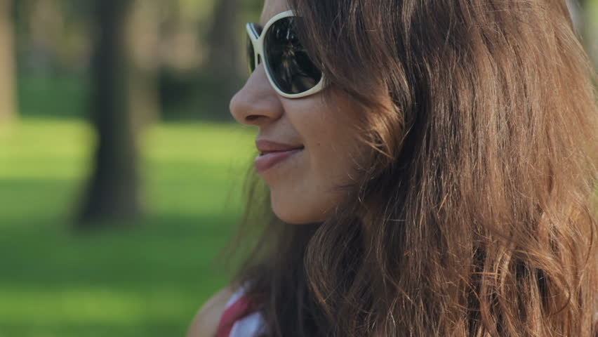 Happy young woman in sunglasses at the summer park | Shutterstock HD Video #24253547