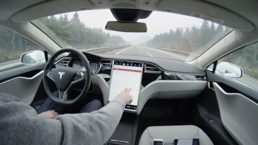 LJUBLJANA, SLOVENIA - FEBRUARY 4, 2017: Tesla autopilot self-driving in severe weather condition with no human intervention. Driver browsing the internet using touchscreen in futuristic autonomous car