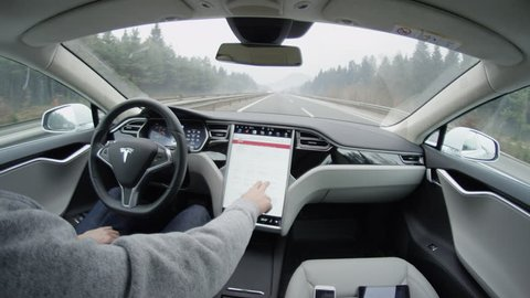 AUTONOMOUS TESLA CAR, FEBRUARY 2016: Tesla autopilot self-driving in severe weather condition with no human intervention. Driver browsing the internet using touchscreen in futuristic autonomous car