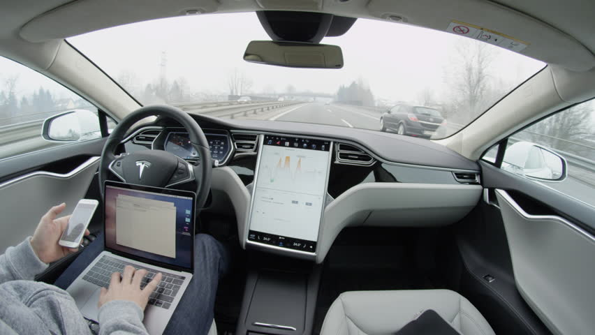 LJUBLJANA, SLOVENIA - FEBRUARY 4, 2017: Self-driving Tesla Model S car autopilot demanding driver attention to hold steering wheel & take control on highway. Man working on laptop & texting on mobile