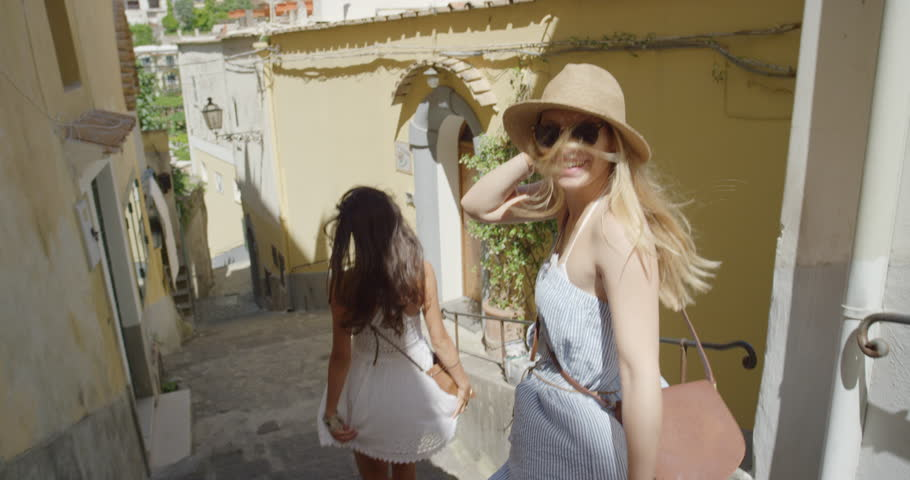 Girl friends walking in Italian street exploring European town Tourist women travelling in beautiful Italy Best friends enjoying summer vacation travel adventure