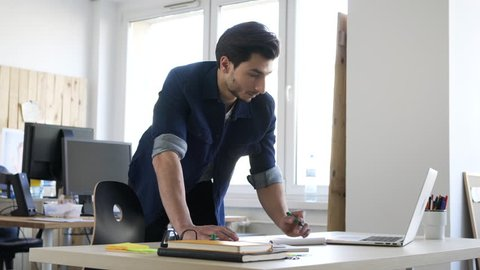 Handsome man, designer working in creative agency office.
