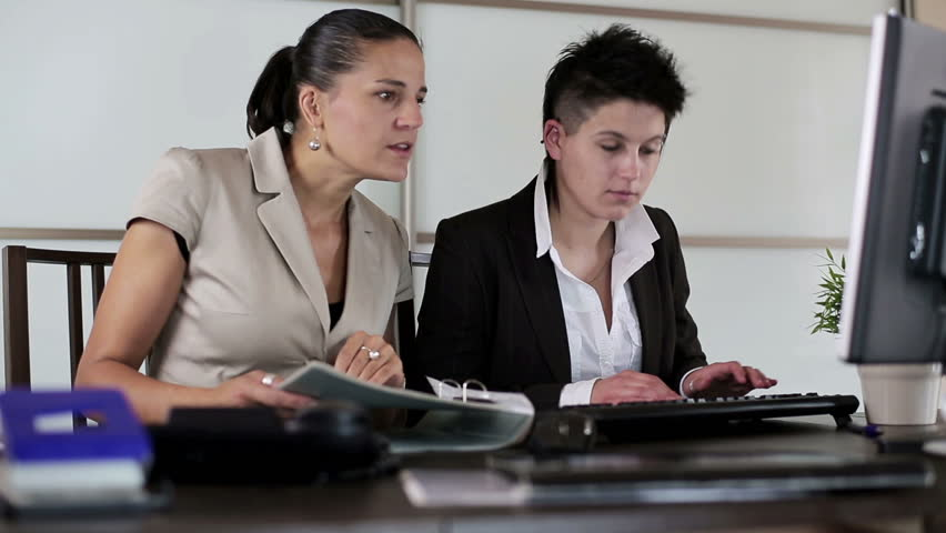 Businesswomen working together with documents in front of computer