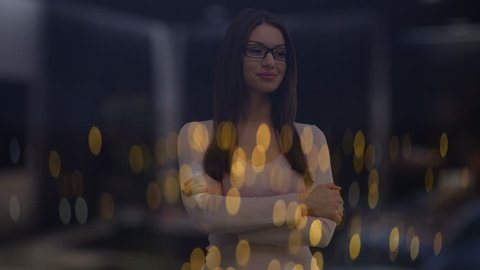 The woman stand near window against the night city lights. Anamorphic lens shot