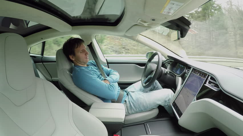 Male driver sleeping behind the self-driving steering wheel of an autonomous autopilot driverless car. Man fell deeply asleep while driving along the countryside road in luxury all-electric vehicle