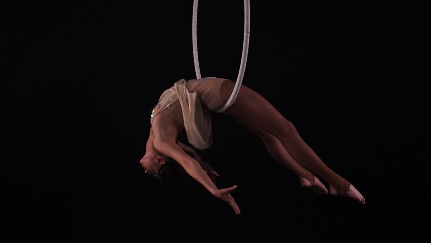 Young caucasian brunette sportive dancer female balancer in beige leotard back lying hang on aerial hoop on black background, slowmotion