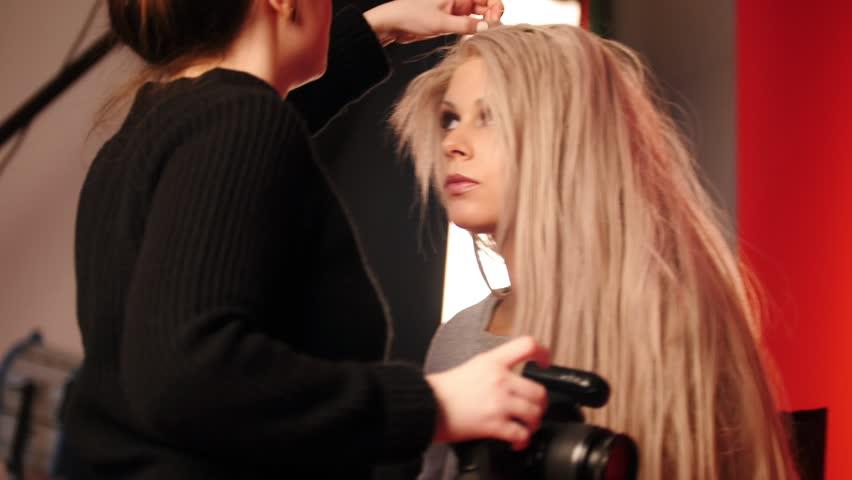 Blonde model girl in photo studio - photographer straightens hair, fashion backstage   Shutterstock HD Video #24328997