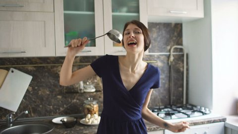 Funny woman housewife cook dance and sing with big ladle while cooking in modern kitchen at home