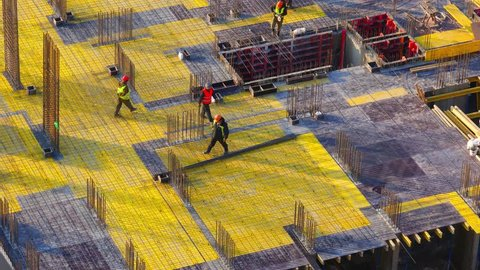 Top view of a group of construction workers at construction site. Builders laids metal reinforcements for the new floor slabs. Zoom out effect from the bottom point. Time lapse