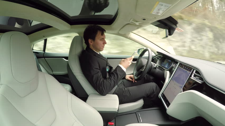 CLOSE UP: Young businessman texting writing messages on mobile phone while sitting behind self-driving steering wheel in autonomous autopilot driverless electric car traveling along countryside road | Shutterstock HD Video #24380111