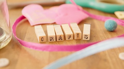 A hand puts the finishing touches on an inspiring message, made out of wooden letter blocks on a wooden craft table, bursting with pretty craft supplies, in an artists' studio. Crafts.