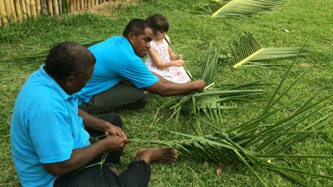 Fijian men teach young tourist girl how to create a basket from weaving a Coconut Palm leaves.Travel Fiji concept, Real people copy space
