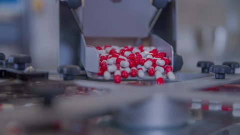 Red-and-white pills are slowly falling on a conveyor belt. They they will be sorted into separate small cups.