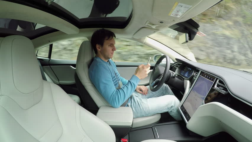 Male driver writing messages on smartphone sitting behind self-driving steering wheel in autonomous autopilot driverless electric car traveling along the countryside road. Man texting in the vehicle #24395867