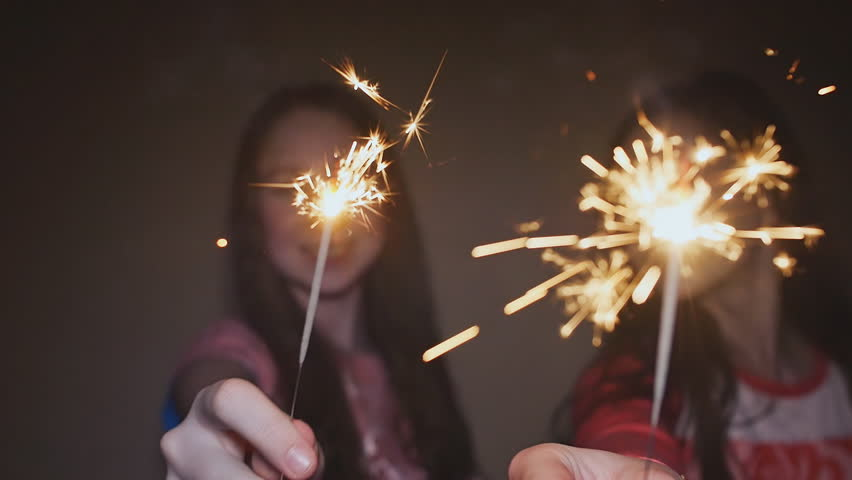 Two teen girls posing and laughing with burning sparklers. | Shutterstock HD Video #24401561