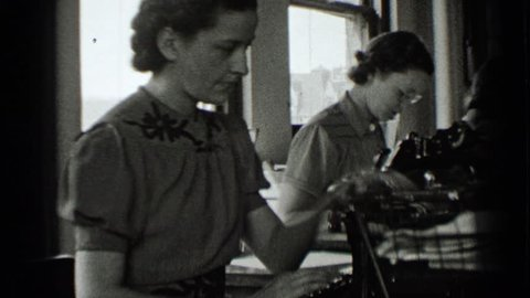 NEW YORK 1939: distracted woman sits in office with coworkers handling clerical work