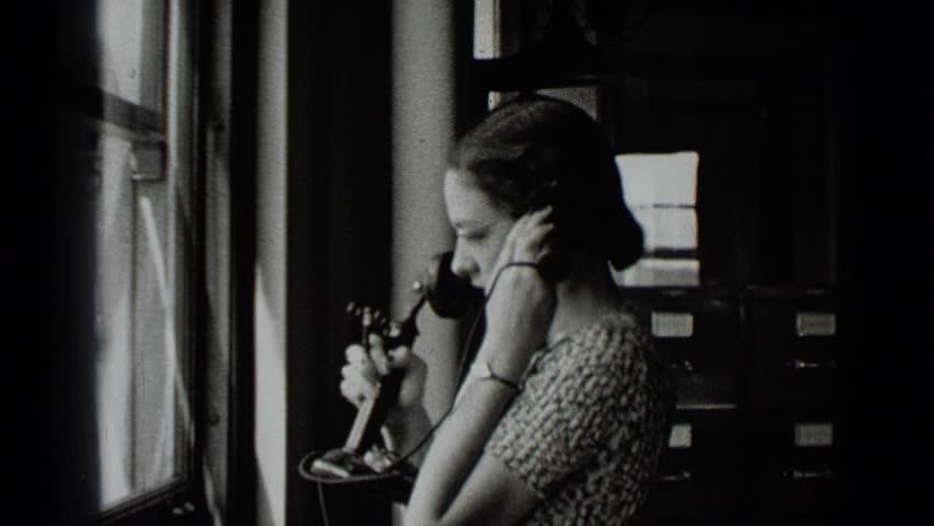 NEW YORK 1939: woman facing window talks on telephone, then turns to camera