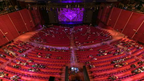 Spectators gather in the auditorium and watch the show in theatre timelapse. Large hall with red armchairs seats. Viewers filling places until turn off the light. View from top