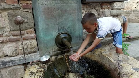 boy drinking water and washing hands from ancient oriental tap in the old city of Nesebar, Bulgaria