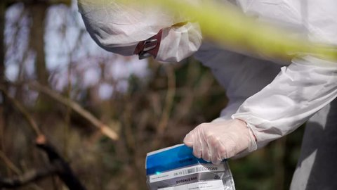 Forensic Scientist Working On Police Investigation Crime Scene Site. A Caucasian White man wearing white protective clothing to limit contamination. Collects evidence in bag, DNA, hair fibres