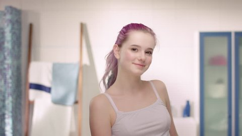 Young girl in puberty using antiperspirant in a modern bathroom
