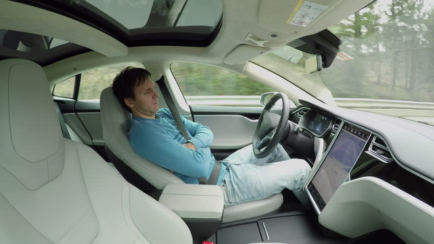 Male driver sleeping behind the self-driving steering wheel of an autonomous autopilot driverless car. Man fell deeply asleep while driving along the countryside road in luxury all-electric vehicle #24508487