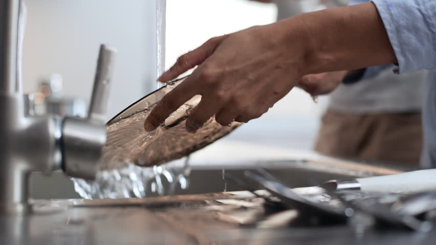 Close up footage of African American female's hands washing glass dishes under water jet in slowmotion
