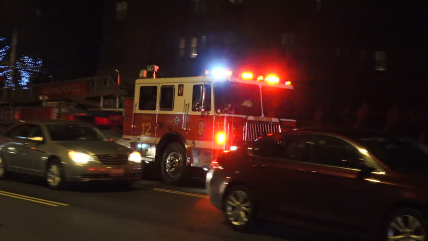 WASHINGTON, DC - FEB. 28, 2017: WASHINGTON, DC - FEB. 28, 2017: Aerial fire truck passes, siren, at night fire scene. As engine passes, see 2nd aerial truck w ladder raised at apartment building.