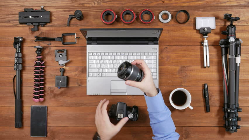 Hands of male photographer. camera lens removed for cleaning. Wooden table top view. Equipment for shooting video on the table | Shutterstock HD Video #24522437