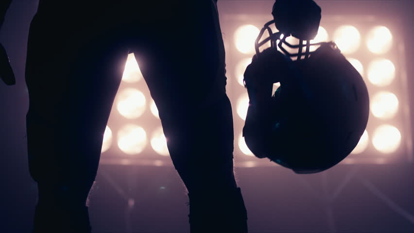 Silhouette of male American football player walking towards camera against bright stadium illumination lights. Bearded man. 4K UHD RAW edited footage #24525797