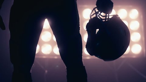 Silhouette of male American football player walking towards camera against bright stadium illumination lights. Bearded man. 4K UHD RAW edited footage