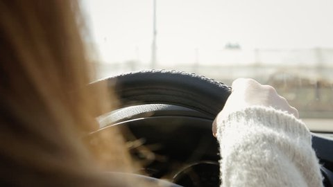 The hands of a woman driving a car, seen from behind (rear seats). Orange daylight tones.