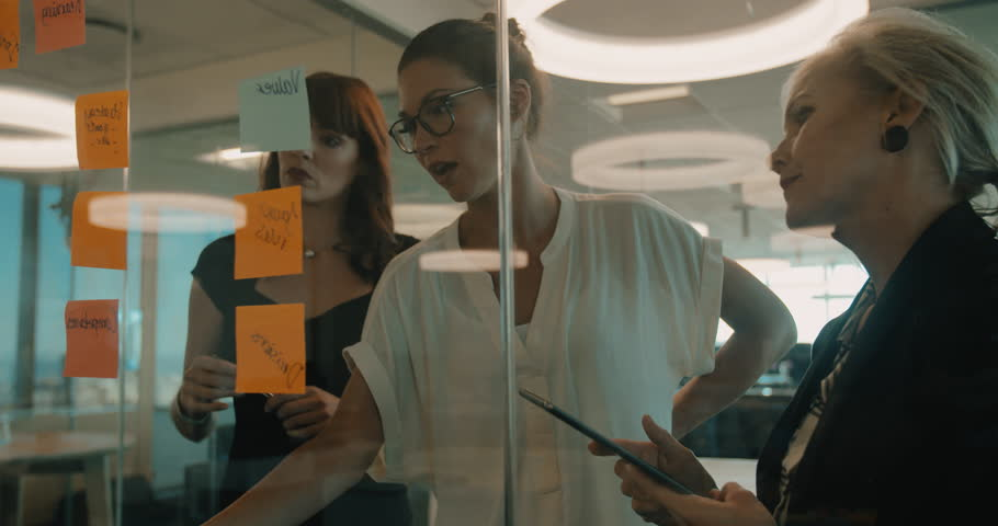 Three business women having a meeting in office. They are standing in front of glass wall with post it notes.
