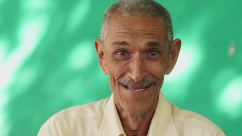 Real Cuban elderly people and feelings, portrait of happy old hispanic man with mustache from Havana, Cuba looking at camera, laughing and smiling