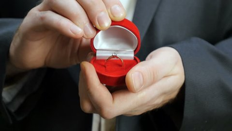 The groom opens the box with a wedding ring.