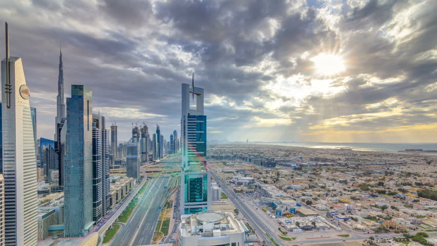 Dubai skyscrapers sunset timelapse evening time. Dubai Metro station and traffic on Sheikh Zayed Road. Aerial top view drom tower rooftop. Beautiful colorful cloudy sky with rays of sun light
