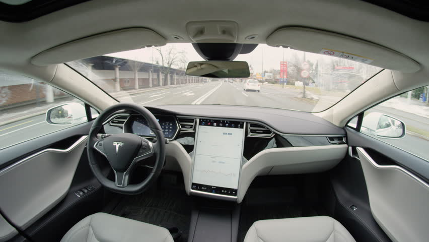 LJUBLJANA, SLOVENIA - FEBRUARY 4, 2017: Fully autonomous self-driving autopilot Tesla Model S driverless car maneuvering on local street in urban city. Enhanced next gen intelligent robotic vehicle