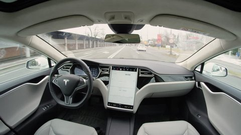 LJUBLJANA, SLOVENIA - FEBRUARY 4, 2017: Fully autonomous self-driving autopilot Tesla Model S driverless car maneuvering on local street in urban city. Enhanced next gen intelligent robotic vehicle