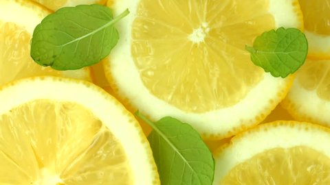 Lemon slices with mint leaf rotation background. Close-up of a delicious ripe lemon rotate and aromatic mint. Healthy food, cooking ingredient. UHD video footage. Ultra high definition 3840X2160