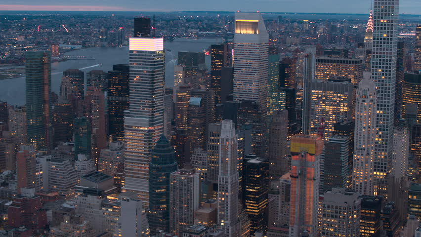 AERIAL HELI SHOT: Huge shining glassy skyscrapers, lit contemporary office buildings and luxury condo towers rising above low-rise blocks of flats in Midtown Manhattan New York City at pik light dawn | Shutterstock HD Video #24621317