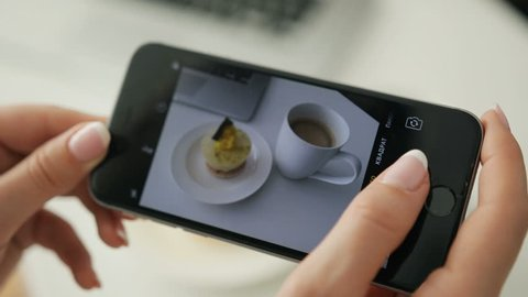 Woman taking picture of her breakfast by her smart phone