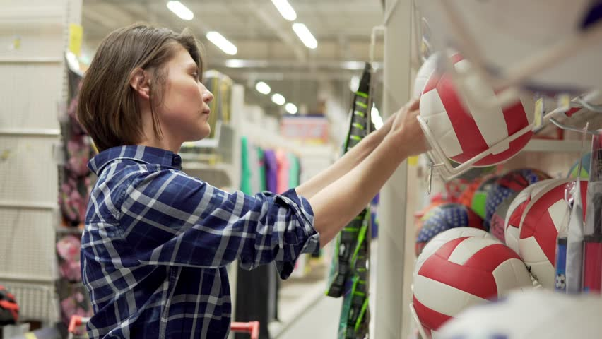 Young woman selecting sport equipment in supermarket. Choosing ball for soccer or football | Shutterstock HD Video #24643247
