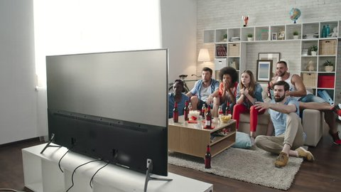 Multi-ethnic group of young flat mates watching sports competition on TV at home. They jumping up, raising hands and yelling while celebrating goal of favorite team