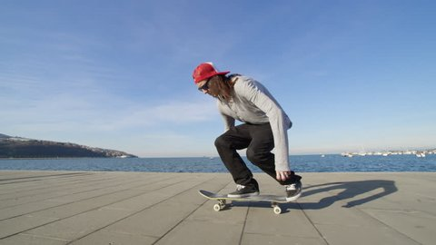 CLOSE UP SLOW MOTION: Young pro skateboarder skateboarding and jumping ollie flip trick on promenade along the coast in sunny summer. Skateboarder jumping kickflip trick with skateboard near the ocean