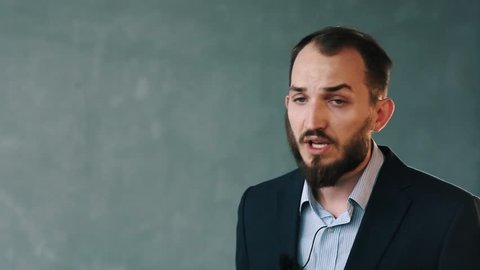 Young caucasian bearded man in blue business jacket and striped shirt with lavalier microphone on isolated background wall shares opinion holding camcorder in hands